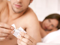 couple-bed-condom-intercourse