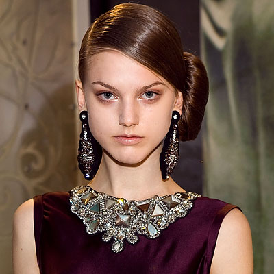 To recreate this look, start by making a deep side part and smoothing the