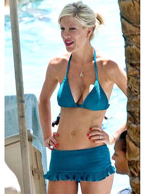 Com uma silhueta esbelta e cabelo pintado sem sutiã (tamanho 34C) em biquini na praia