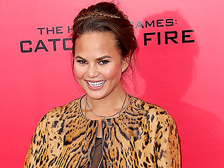 Why Is Chrissy Teigen Burying a Book on the Beach?