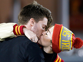 Miley Cyrus & Patrick Schwarzenegger Share a Sweet Kiss at USC Game (PHOTO)