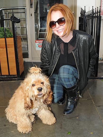 Η  Lindsay χαμογελάει και φωτογραφίζεται με ένα σκύλο...