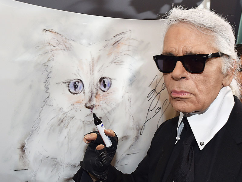 Karl Lagerfeld poses next to a painting of his cat