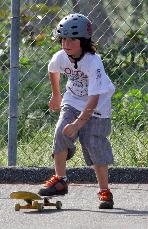 Kid Skateboards Over Rock