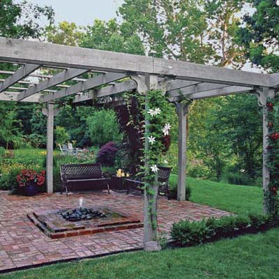 pergola with climbing perennial vines surround a brick patio with benches and fountain