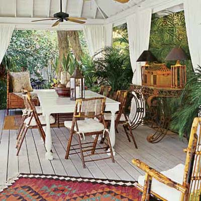 a covered patio furnished in the British Colonial style