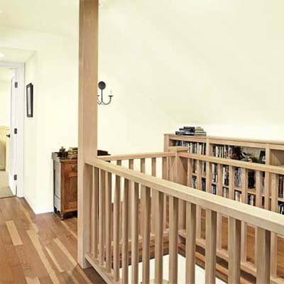 low bookcases built along the walk space topping the stairs in this attic remodel