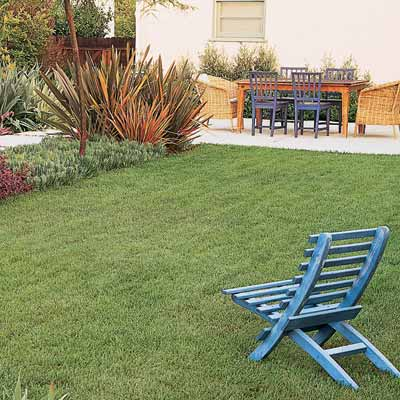 lush lawn with blue chair and dining patio in the distance