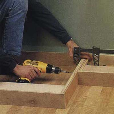 Installing the toekick of a custom entertainment center with drill