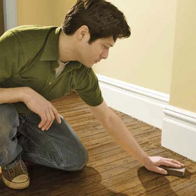 sanding a wood floor with a sanding sponge