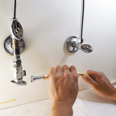 man inserting tube spring in water supply
