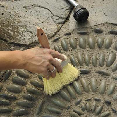 Mark Powers using a stiff-bristled brush to dress and shape the joints of his pebble mosaic